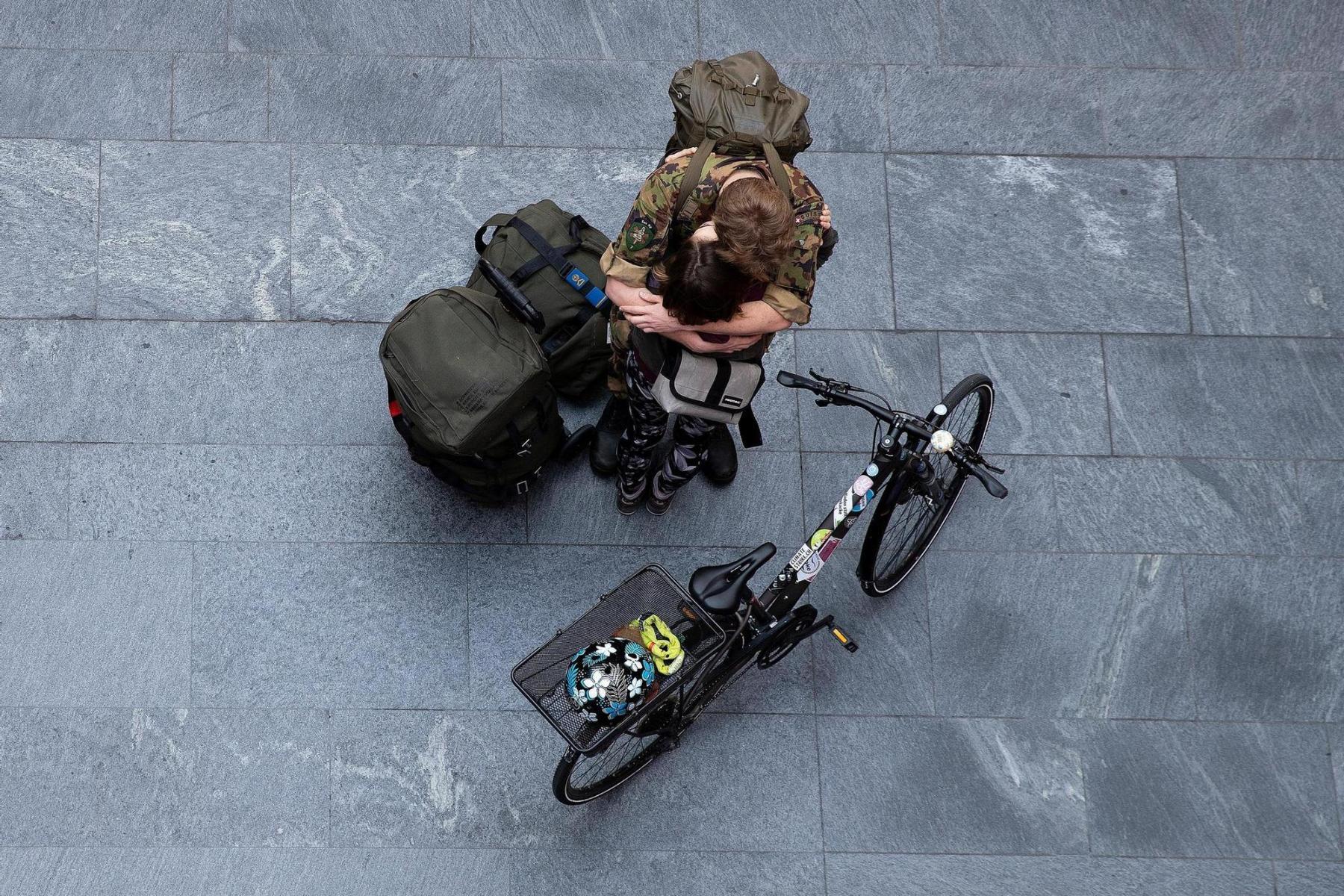 Ein Leutnant der Sanitätstruppen verabschiedet sich am 17.3.2020 im Bahnhof Bern auf unbestimmte Zeit. Niemand weiss, was kommt. Es sind Leute, welche aus ihrem vertrauten Umfeld gerissen wurden, ihr Umfeld vermissen und von ihrem Umfeld vermisst werden. Foto: Christian Pfander