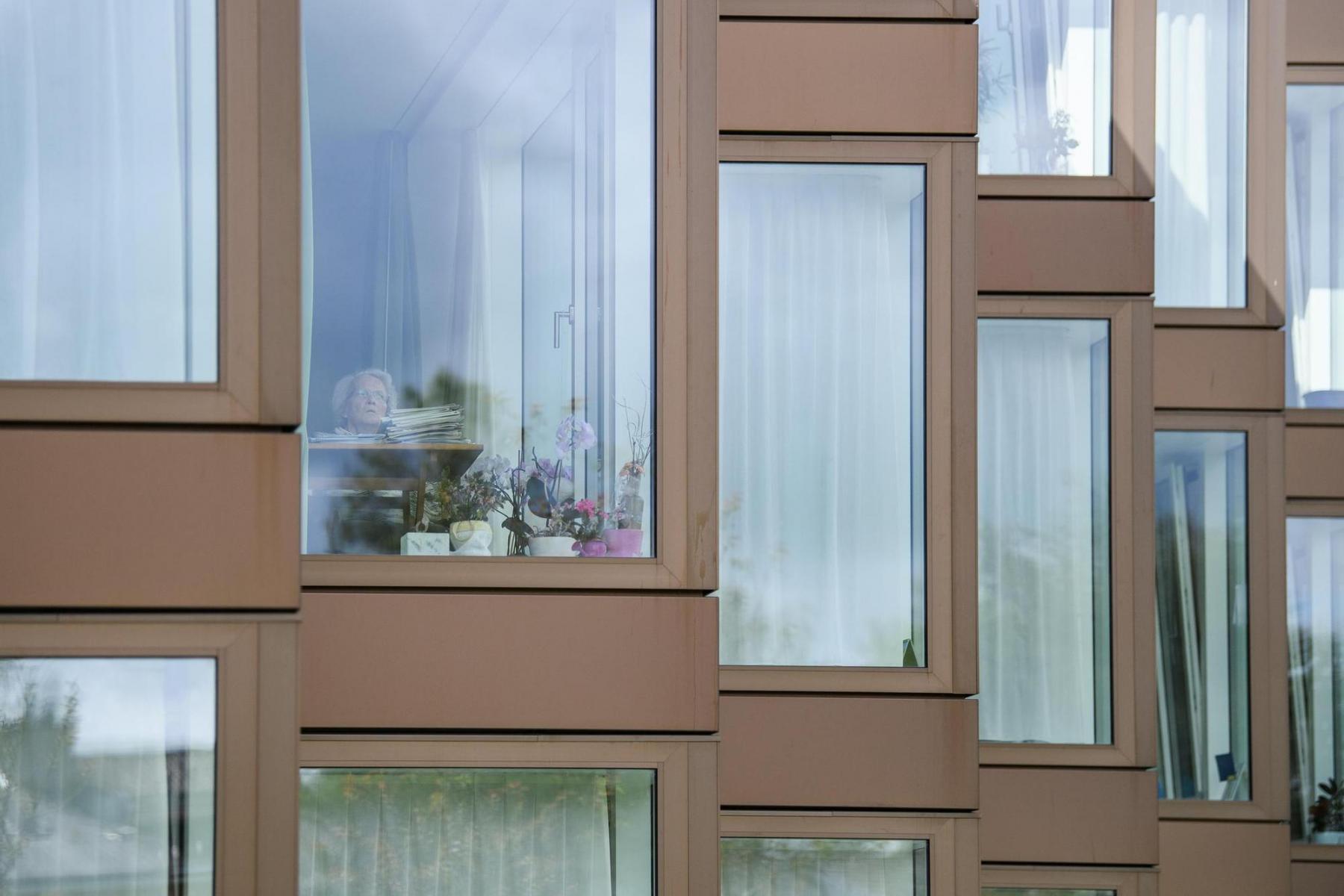 Angehörige in Alten- und Pflegeheimen erhalten keinen Besuch mehr. Er ist untersagt. Hier schaut eine Bewohnerin des Pflegeheims Ruferheim aus dem Fenster. Aufgenommen am 29.4.2020 in Nidau. Foto: Raphael Moser